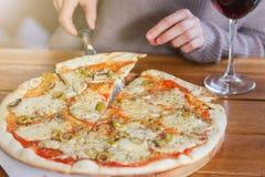 Η γυναίκα παίρνει μια φέτα της τεμαχισμένης πίτσας με τη μοτσαρέλα στοκ εικόνα