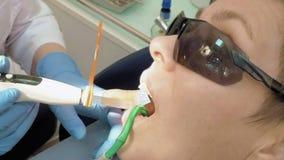 Η γυναίκα παίρνει την οδοντική βοήθεια για να γεμίσει μια κοιλότητα σε ένα δόντι απόθεμα βίντεο