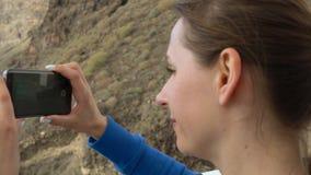 Η γυναίκα παίρνει τη φωτογραφία των απότομων βράχων Los Gigantes Tenerife, Κανάρια νησιά, Ισπανία απόθεμα βίντεο