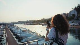 Η γυναίκα παίρνει τις εικόνες των δεμένων γιοτ στο λιμένα πόλεων από τη κάμερα κινητού απόθεμα βίντεο