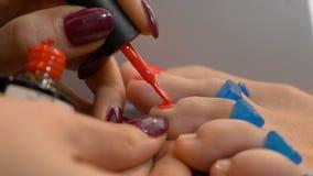 Η γυναίκα παίρνει το επαγγελματικό pedicure με μια κομψή κόκκινη στιλβωτική ουσία καρφιών φιλμ μικρού μήκους