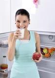 Η γυναίκα παίρνει το κόκκινα μήλο και το γάλα από το ψυγείο Στοκ εικόνες με δικαίωμα ελεύθερης χρήσης