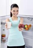 Η γυναίκα παίρνει το κόκκινα μήλο και το γάλα από το ψυγείο Στοκ Εικόνα