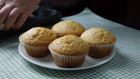Η γυναίκα παίρνει φρέσκα ψημένα muffins από muffins τον κασσίτερο και τα τοποθετεί στο πιάτο απόθεμα βίντεο