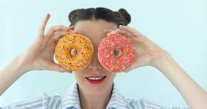 Η γυναίκα παίρνει donuts και κάνει τα γυαλιά ηλίου από το Στοκ Εικόνες