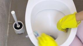 Η γυναίκα παραδίδει ένα κίτρινο γάντι που καθαρίζει το κύπελλο τουαλετών απόθεμα βίντεο