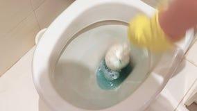 Η γυναίκα παραδίδει το κίτρινο λαστιχένιο γάντι που καθαρίζει ένα βρώμικο κύπελλο τουαλετών με μια βούρτσα απόθεμα βίντεο