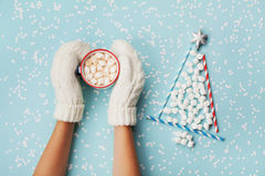 Η γυναίκα παραδίδει το φλυτζάνι λαβής γαντιών του καυτής κακάου ή της σοκολάτας και το δέντρο έλατου Χριστουγέννων φιαγμένο από δ Στοκ εικόνα με δικαίωμα ελεύθερης χρήσης