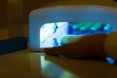 Η γυναίκα παραδίδει το UV οδηγημένο μανικιούρ πηκτωμάτων ξήρανσης λαμπτήρων Στοκ Φωτογραφία