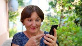 Η γυναίκα παρουσιάζει στο τηλεφωνικό εξωτερικό smartphone κοντά στο σπίτι φιλμ μικρού μήκους