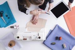 Η γυναίκα παρουσιάζει ταμπλέτα στο ράβοντας συνάδελφό της Στοκ εικόνες με δικαίωμα ελεύθερης χρήσης