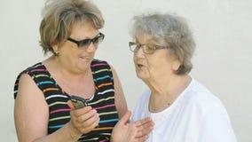 Η γυναίκα παρουσιάζει φωτογραφία στη ηλικιωμένη γυναίκα χρησιμοποιώντας ένα smartphone φιλμ μικρού μήκους
