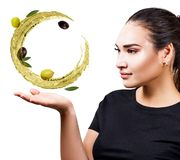 Η γυναίκα παρουσιάζει ότι κυκλοφορήστε τον παφλασμό του ελαιολάδου με τις ελιές διαθέσιμες στοκ φωτογραφία