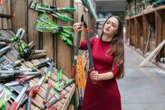 Η γυναίκα πελατών αγοράζει τα εργαλεία συντήρησης κήπων Στοκ Εικόνα