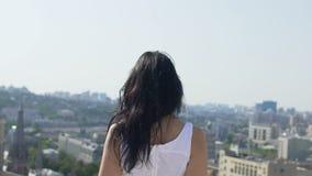 Η γυναίκα περπατά μακριά προς την άκρη του κτηρίου, προετοιμάζοντας το άλμα αυτοκτονίας, πόλη πίσω απόθεμα βίντεο