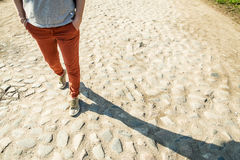 Η γυναίκα περπατά την άνοιξη την ηλιόλουστη ημέρα στον παλαιό δρόμο πετρών Στοκ εικόνα με δικαίωμα ελεύθερης χρήσης