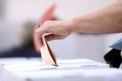 Η γυναίκα πετά την ψήφο της στις εκλογές στοκ φωτογραφία