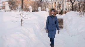 Η γυναίκα πηγαίνει κάτω σε μια χιονώδη σκάλα, σκάλα Χειμερινό πάρκο στην πόλη κατά τη διάρκεια της ημέρας στο χιονώδη καιρό με το απόθεμα βίντεο
