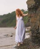 Η γυναίκα πηγαίνει κατά μήκος της ακτής στοκ εικόνες