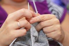 Η γυναίκα πλέκει με το πλέξιμο του γκρίζου πουλόβερ βελόνων από το φυσικό μαλλί Στοκ Φωτογραφία