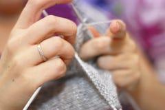 Η γυναίκα πλέκει με το πλέξιμο του γκρίζου πουλόβερ βελόνων από το φυσικό μαλλί Στοκ φωτογραφίες με δικαίωμα ελεύθερης χρήσης