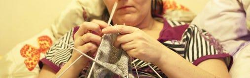 Η γυναίκα πλέκει με το πλέξιμο του γκρίζου πουλόβερ βελόνων από το φυσικό μαλλί Στοκ Εικόνες