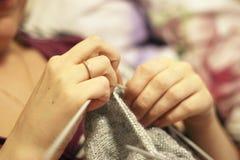 Η γυναίκα πλέκει με το πλέξιμο του γκρίζου πουλόβερ βελόνων από το φυσικό μαλλί Στοκ εικόνες με δικαίωμα ελεύθερης χρήσης