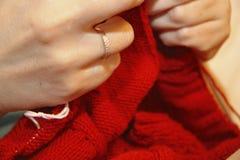 Η γυναίκα πλέκει με το πλέξιμο του κόκκινου πουλόβερ βελόνων από το φυσικό woole Στοκ φωτογραφία με δικαίωμα ελεύθερης χρήσης