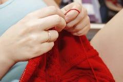 Η γυναίκα πλέκει με το πλέξιμο του κόκκινου πουλόβερ βελόνων από το φυσικό woole Στοκ Εικόνα