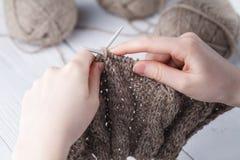 Η γυναίκα πλέκει τα μάλλινα ενδύματα Πλέκοντας βελόνες Κινηματογράφηση σε πρώτο πλάνο Φυσικό μαλλί Στοκ Εικόνα