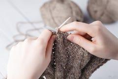 Η γυναίκα πλέκει τα μάλλινα ενδύματα Πλέκοντας βελόνες Κινηματογράφηση σε πρώτο πλάνο Φυσικό μαλλί Στοκ Φωτογραφίες