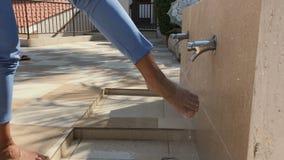 Η γυναίκα πλένει τα πόδια υπαίθρια απόθεμα βίντεο