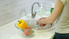 Η γυναίκα πλένει τα φρέσκα λαχανικά κάτω από τη βρύση στο νεροχύτη στην κουζίνα τα βάζει σε ένα φλυτζάνι γυαλιού φιλμ μικρού μήκους