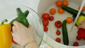 Η γυναίκα πλένει τα φρέσκα λαχανικά κάτω από τη βρύση στο νεροχύτη στην κουζίνα τα βάζει σε ένα φλυτζάνι γυαλιού απόθεμα βίντεο