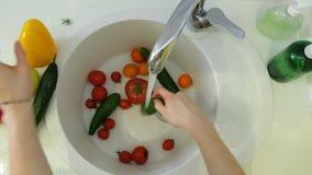 Η γυναίκα πλένει τα φρέσκα λαχανικά κάτω από τη βρύση στο νεροχύτη στην κουζίνα απόθεμα βίντεο