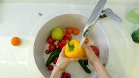 Η γυναίκα πλένει τα φρέσκα λαχανικά κάτω από τη βρύση στο νεροχύτη στην κουζίνα φιλμ μικρού μήκους