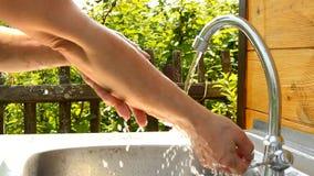 Η γυναίκα πλένει τα χέρια της κάτω από το τρεχούμενο νερό από την υπαίθρια βρύση στον κήπο τη θερινή ηλιόλουστη ημέρα, το καθαρό  απόθεμα βίντεο