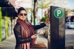 Η γυναίκα πληρώνει για το χώρο στάθμευσης στοκ εικόνες