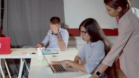 Η γυναίκα πλησιάζει στη γυναίκα εργαζόμενος στην αρχή και διαγράμματα εξέτασης στο lap-top απόθεμα βίντεο