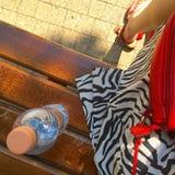 Η γυναίκα που έχει το καλοκαίρι χαλαρώνει σε έναν πάγκο Στοκ εικόνα με δικαίωμα ελεύθερης χρήσης