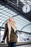 Η γυναίκα που εξετάζει το ρολόι στο σταθμό τρένου ως τραίνο της έχει μια καθυστέρηση στοκ φωτογραφία