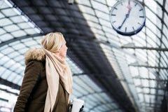 Η γυναίκα που εξετάζει το ρολόι στο σταθμό τρένου ως τραίνο της έχει μια καθυστέρηση στοκ εικόνα με δικαίωμα ελεύθερης χρήσης