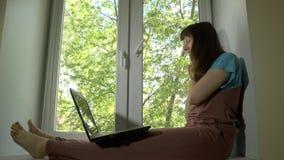 Η γυναίκα που εργάζεται και επικοινωνεί πίσω από το lap-top στο windowsill φιλμ μικρού μήκους