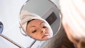 Η γυναίκα που εφαρμόζει την κρέμα προσώπου στο δέρμα Καυκάσιο θηλυκό μπροστά από τον καθρέφτη σύνθεσης απόθεμα βίντεο