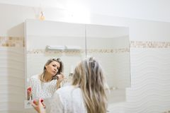Η γυναίκα που εφαρμόζει το πρωί αποτελεί στον καθρέφτη του λουτρού στοκ φωτογραφία με δικαίωμα ελεύθερης χρήσης