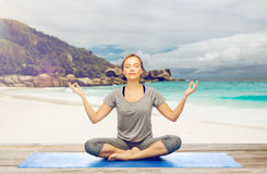 Η γυναίκα που κάνει την περισυλλογή γιόγκας στο λωτό θέτει στην παραλία στοκ εικόνα με δικαίωμα ελεύθερης χρήσης