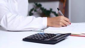 Η γυναίκα που κάνει τους υπολογισμούς στο γραφείο και γράφει τους προκύπτοντες αριθμούς κλείστε επάνω απόθεμα βίντεο