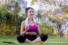 Η γυναίκα που κάνει το posee γιόγκας πρακτικής στο πάρκο, όμορφη νέα συνεδρίαση γυναικών χαλαρώνει το χρόνο γιόγκας στοκ εικόνα