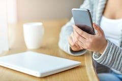 Η γυναίκα που κρατά ένα τηλέφωνο στα χέρια και γράφει το μήνυμα στον καφέ Στοκ Φωτογραφία