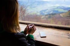 Η γυναίκα που κρατά ένα φλυτζάνι του τσαγιού, κορίτσι φαίνεται έξω το παράθυρο, η άποψη Στοκ Εικόνα